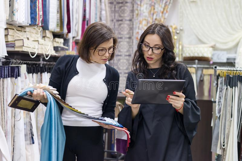 Female salesman and buyer in the fabric store are looking to select samples of materials stock photos