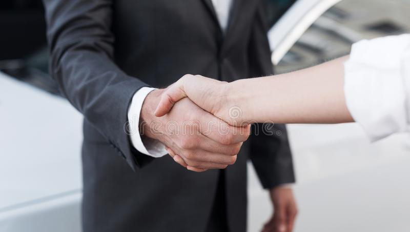 Female salesman shaking hands with customer in dealership. Auto business. Female salesman shaking hands with customer in successful dealership, closeup royalty free stock images
