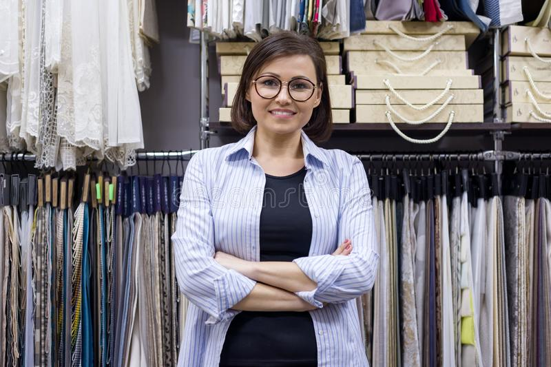 Female saleswoman, interior designer in showroom. Female saleswoman, interior designer posing in showroom, background of book and hanger with fabric samples royalty free stock photo