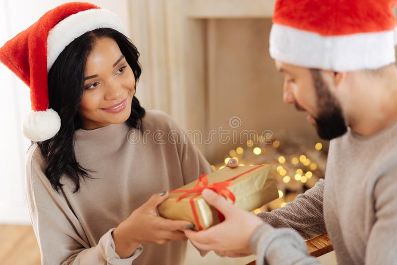 Pleasant woman giving Christmas present to her husband royalty free stock photos