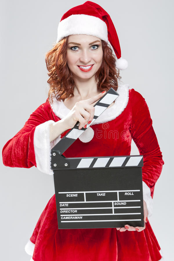 Female Santa Helper Holding Clapperboard in Front Ready to Set o. Ff Filming. Against White Background. Vertical Image Composition royalty free stock photography