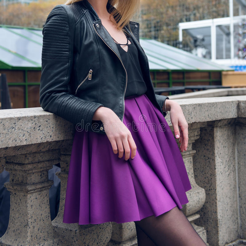 Female scater skirt and leather jacket. Girl wearing fashionable outfit with black leather jacket and purple circle skirt stock image