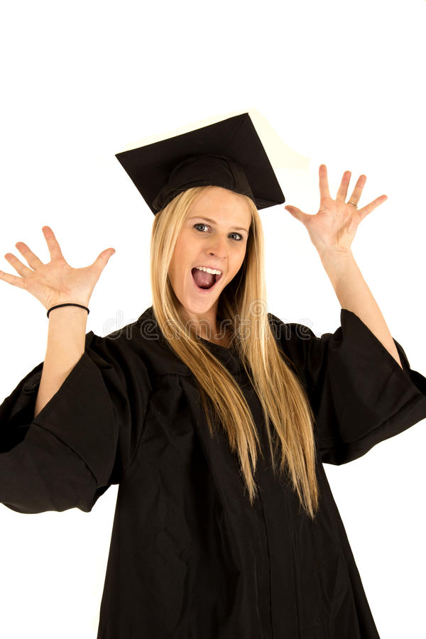 Female school graduate in cap and gown celebrating. High school graduate in cap and gown celebrating royalty free stock image