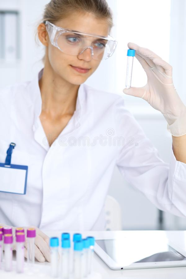 Female scientific researcher in laboratory studying substances or blood sample. Medicine and science concept.  royalty free stock images