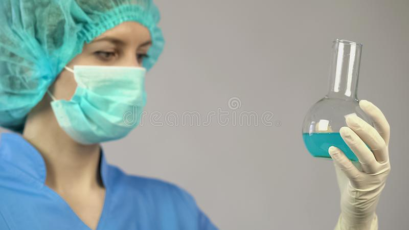 Female scientist analyzing chemical reaction in laboratory tube, experiment stock image