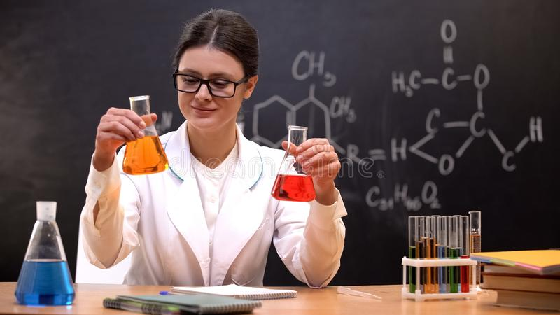 Female scientist comparing flasks with colored liquid, detergent laboratory royalty free stock photos