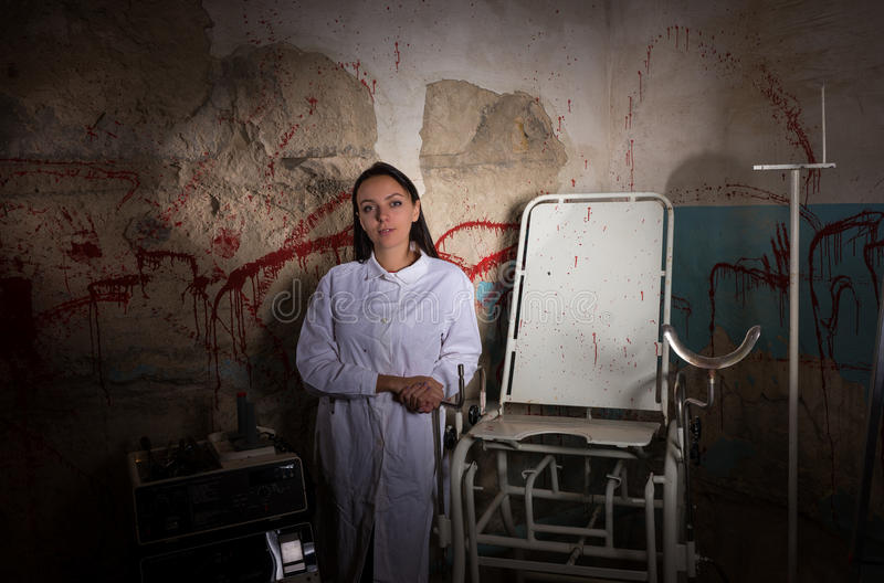 Female scientist in dungeon with bloody walls royalty free stock images