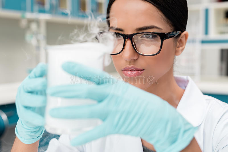 Female scientist in eyeglasses holding flask while making experiment in chemical lab. Young female scientist in eyeglasses holding flask while making experiment royalty free stock images