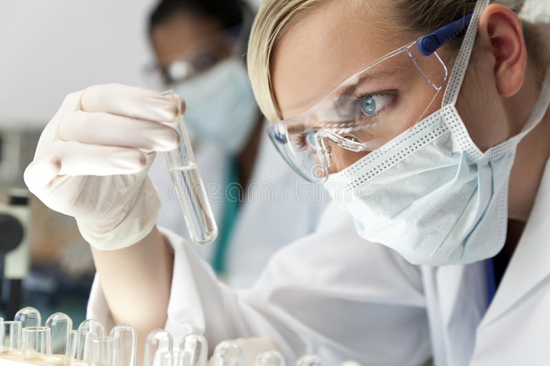 Female Scientist In Laboratory. A blond medical or scientific researcher or doctor using looking at a clear solution in a laboratory with her Asian female stock image