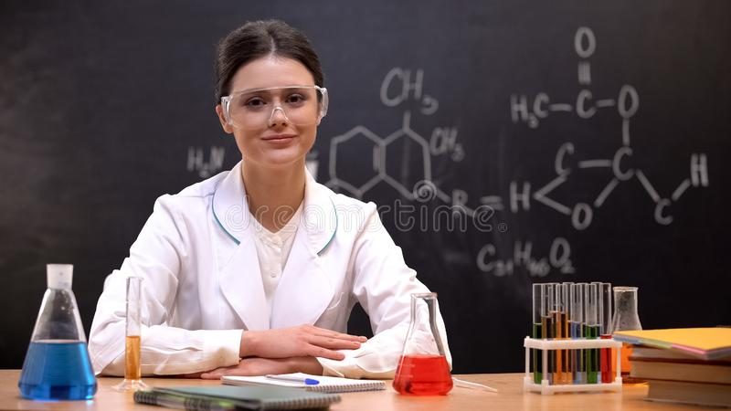 Female scientist in laboratory looking to camera, equipment standing on table stock images