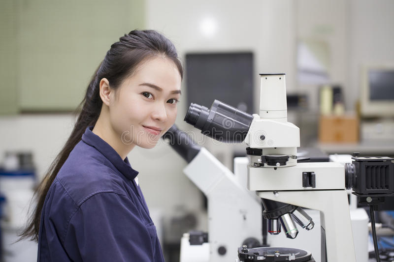 Female scientist looking in microscope in laboratory Laboratory stock image