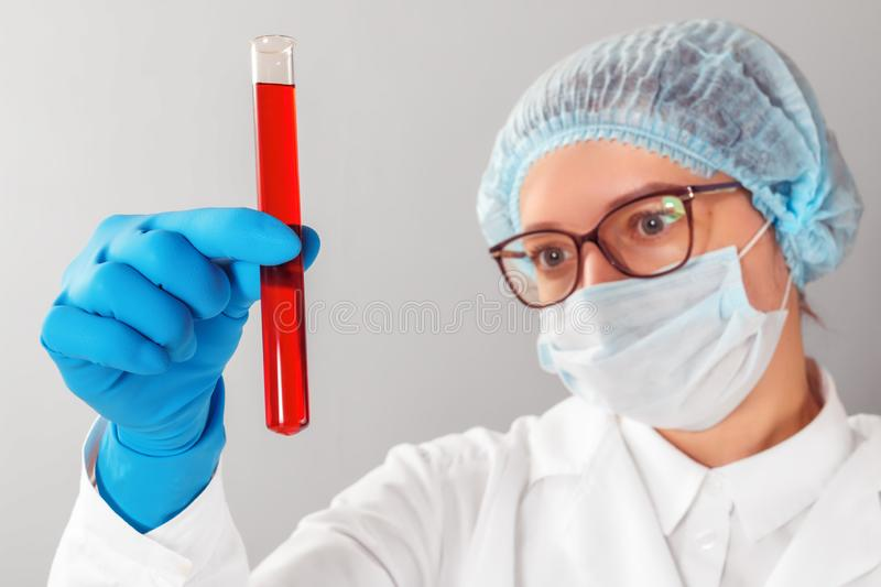Female scientist looking at a test tube in a laboratory stock image