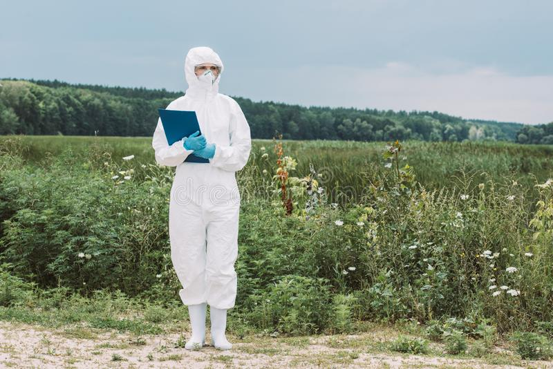 female scientist in protective suit and googles holding clipboard royalty free stock image