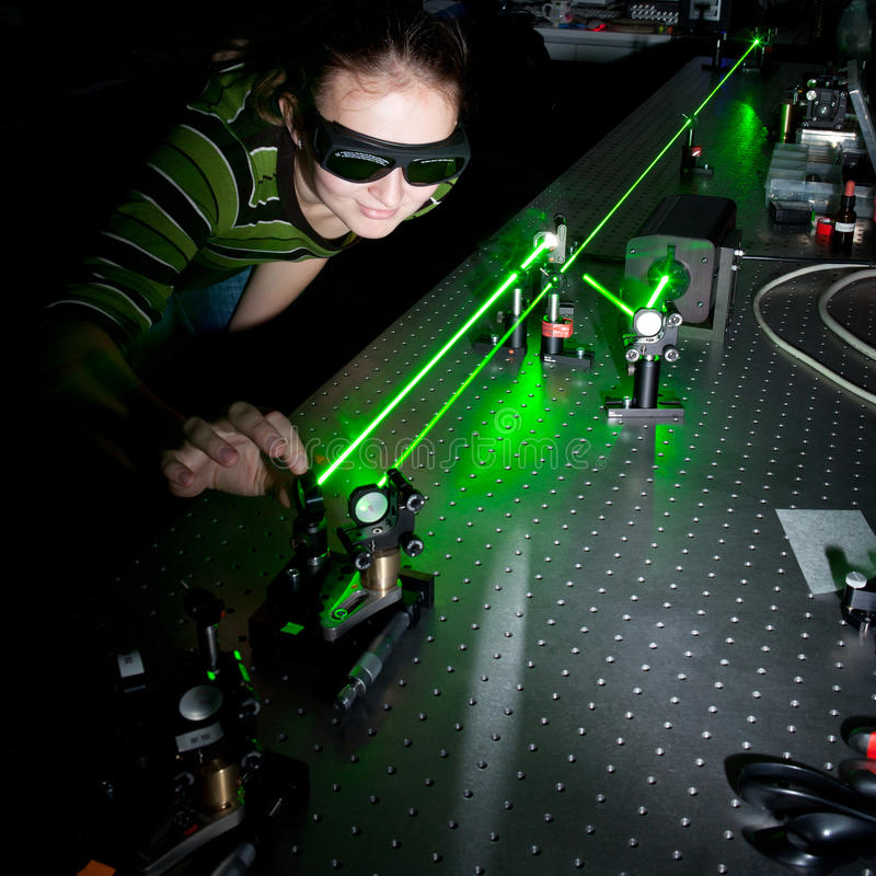 Female scientist in a quantum optics lab. Female scientist doing research in a quantum optics lab royalty free stock photo