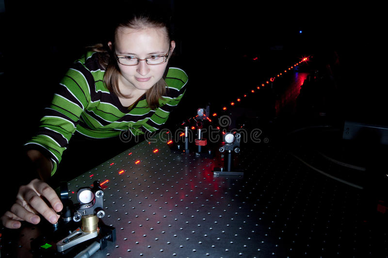 Female scientist in a quantum optics lab. Female scientist doing research in a quantum optics lab stock images