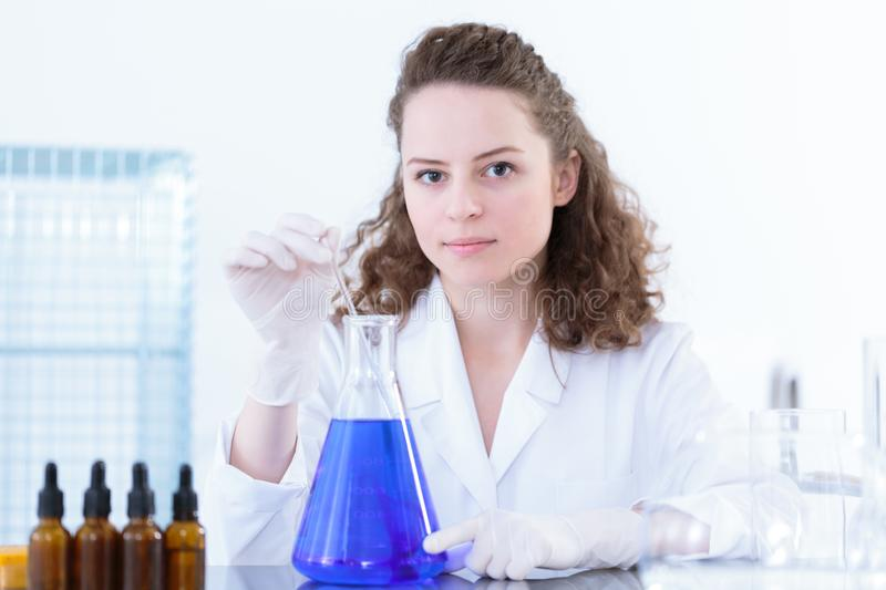 Female scientist stirring blue mixture stock photo