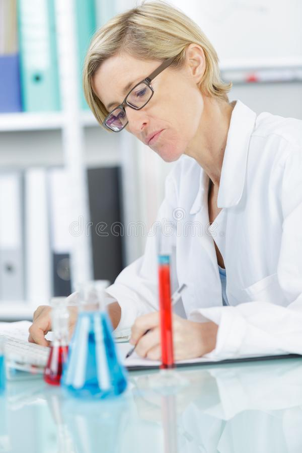 Female scientist writing report on science experiments stock photo