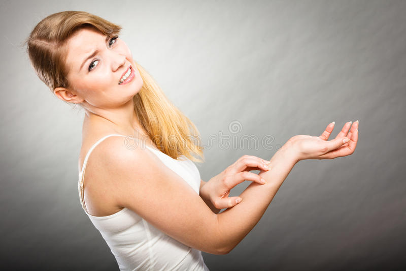 Female scratching her itchy arm with allergy rash. Dermatology, allergy and health problem. Young female scratching her itchy arm with allergy rash royalty free stock photos