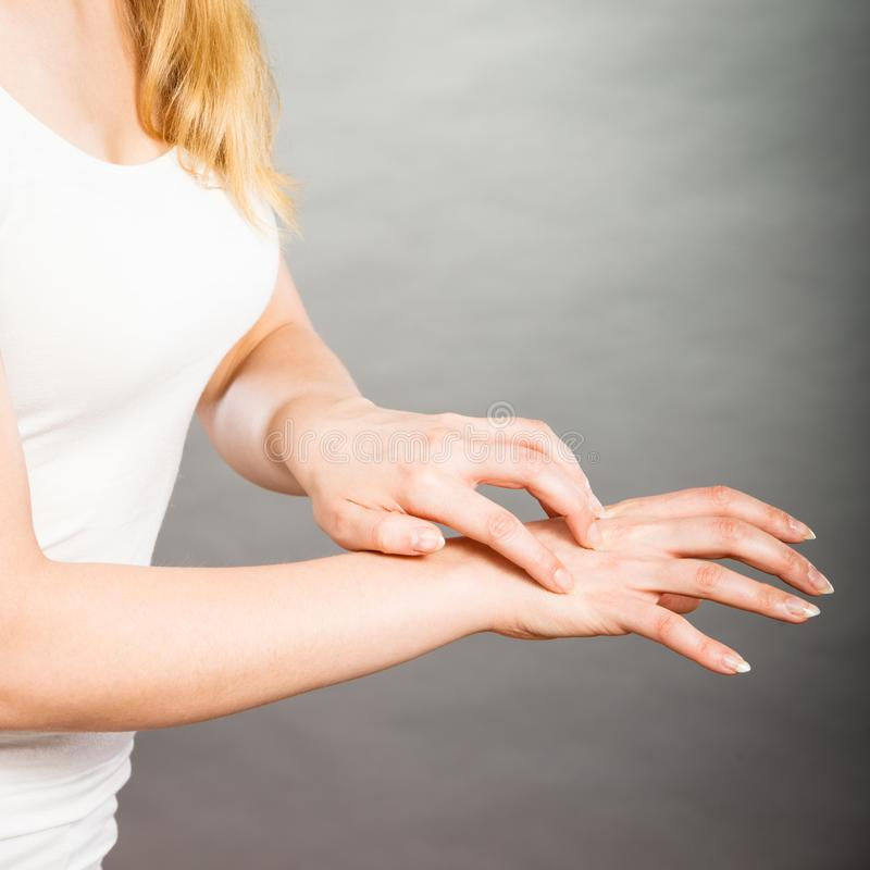 Female scratching her itchy palm with allergy rash. Dermatology, allergy and health problem. Young female scratching her itchy palm with allergy rash stock photography