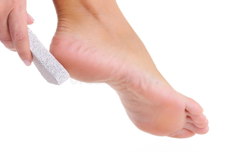 Female scrubbing foot by pumice stock photo