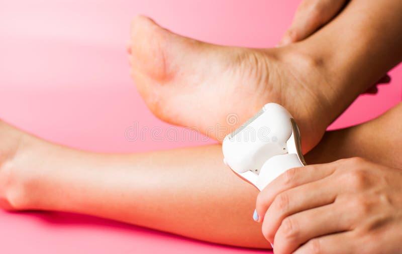 Female scrubbing hard skin from feet stock photo