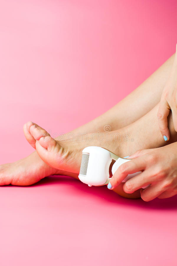 Female scrubbing hard skin from feet. Home pedicure royalty free stock photos