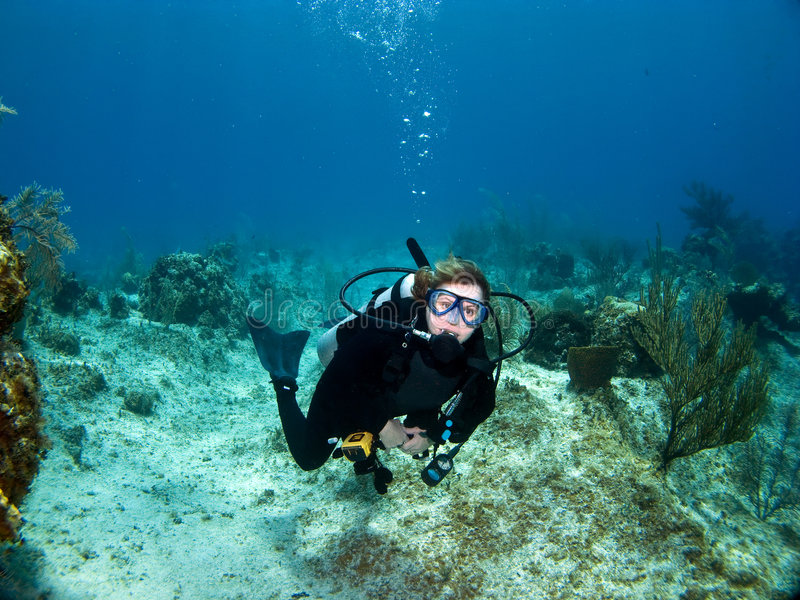 Female Scuba Diver looking at the Camera. Female Scuba Diver swimming while looking at the Camera stock photography