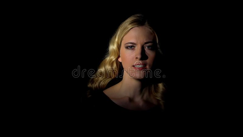 Female secret agent looking at camera in darkness, spying concept, mystery stock photography