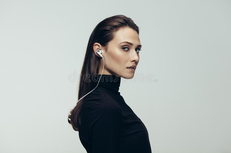 Female secret agent. Portrait of beautiful woman in black top wearing earphones staring at camera. Studio shot of young beautiful woman as secret agent against royalty free stock images