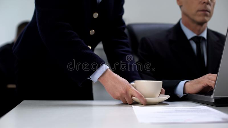 Female secretary bringing boss coffee, company work process, service staff royalty free stock photo