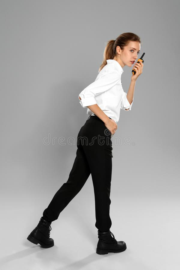 Female security guard in  using portable radio transmitter on grey background stock photos