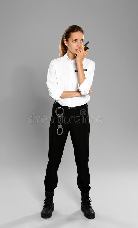 Female security  in uniform using portable radio transmitter on grey background stock images