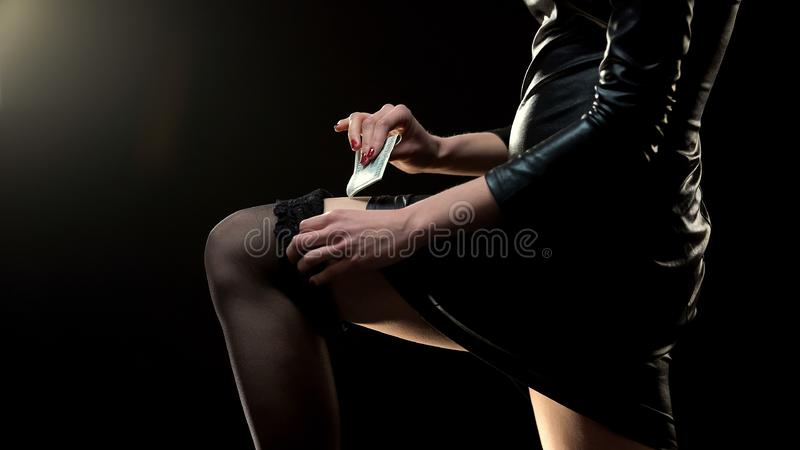 Female in seductive dress putting dollars in stocking, prostitution concept royalty free stock images