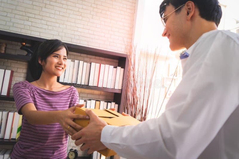 Female seller home business owner handling package to customer stock image