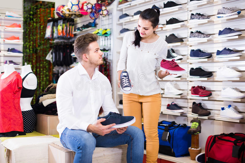Female seller demonstrating sneakers to customer in sports store. Smiling russian female seller demonstrating sneakers to customer in sports store royalty free stock photos