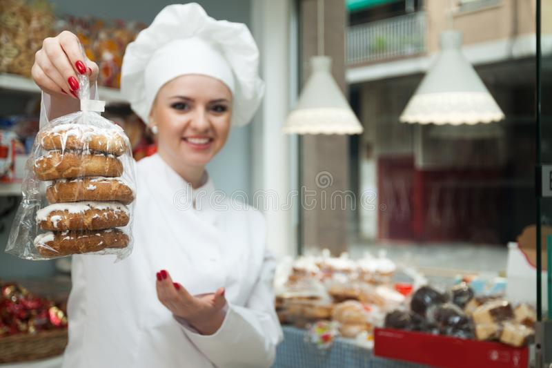 Female seller offering sweets in local confectionery. Young Friendly female seller offering sweets in local confectionery stock photos