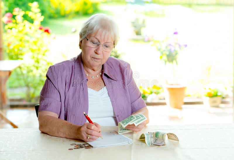 Female senior calculating her budget stock photography