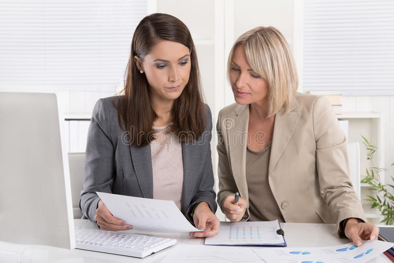 Female senior and junior managers sitting at desk working together in a business team. stock photo