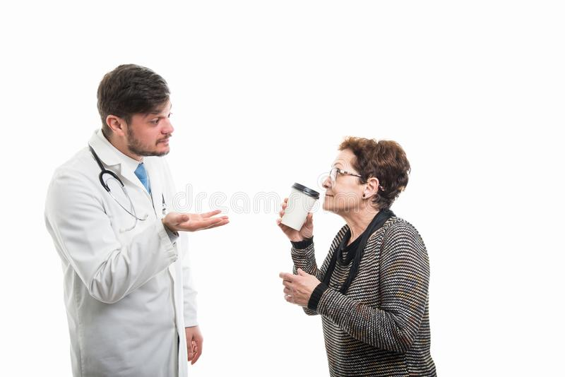 Female senior patient drinking coffee with male doctor royalty free stock images