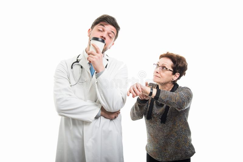 Female senior patient rushing male doctor drinking coffee royalty free stock photo