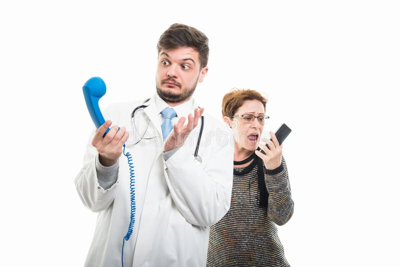 Female senior patient screaming at male doctor to telephone royalty free stock images