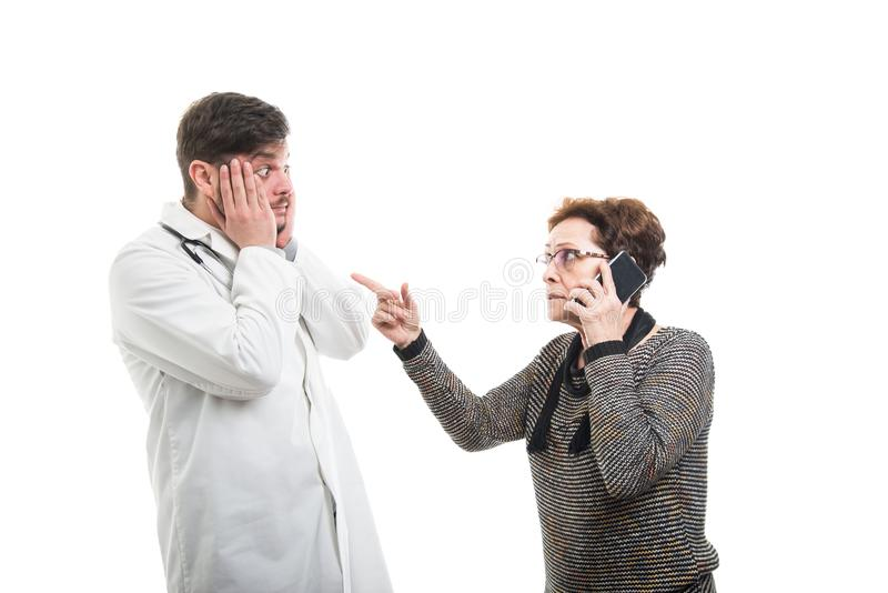 Female senior patient talking at phone pointing male doctor royalty free stock photography