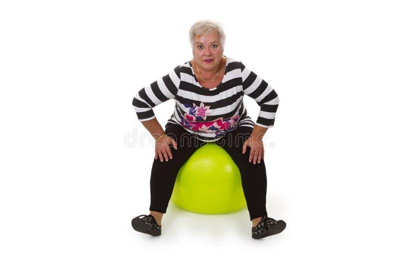 Female senior sitting on swiss ball stock image