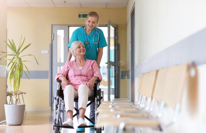 Senior woman in wheelchair with nurse in hospital stock photography