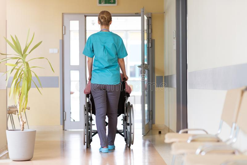 Senior woman in wheelchair with nurse in hospital royalty free stock photography