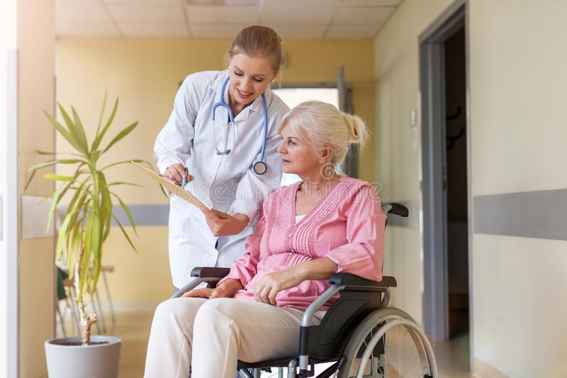 Senior woman in wheelchair with nurse in hospital royalty free stock photo