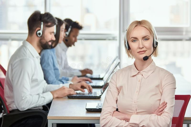 Female serious call center operator with folded arms. Blond mature women with serious face. Bright windows background stock photography