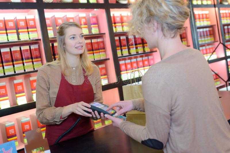 Female serving client paying by credit card at counter. Buying stock photo