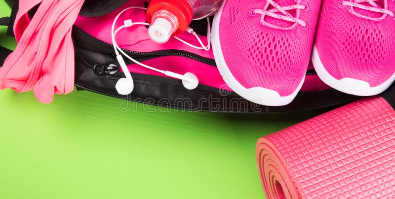 Female set of clothes and accessories in pink for fitness on a green background stock photos