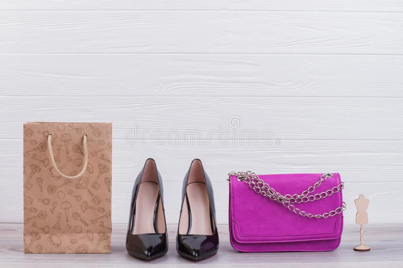 Female shoes, handbag and shopping bag. Black leather heels, pink clutch and kraft paper bag on wooden background. Purchases and shopping concept stock photography